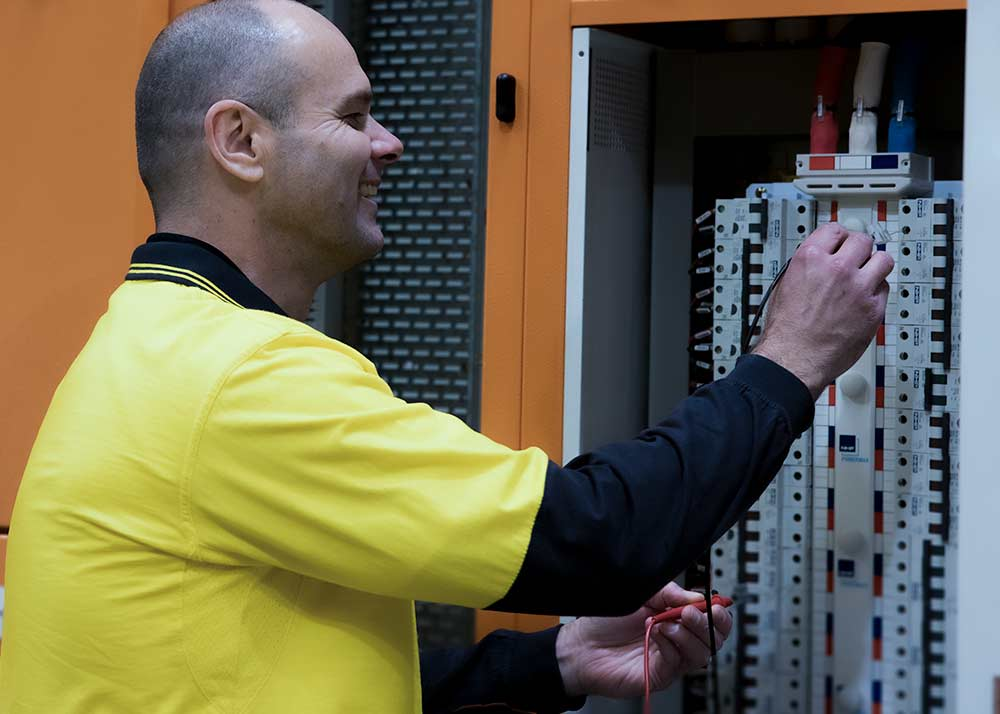 I S Systems Team member working on a switchboard